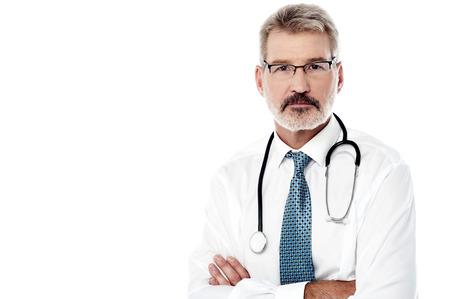 Médico do sexo masculino maduro que levanta com o estetoscópio sobre o branco