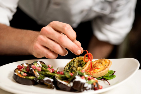 restaurant food: Cropped image of chef garnishing delicious dish Stock Photo