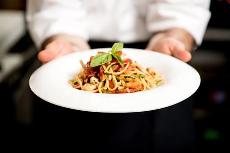 salad plate: Cocinero que sostiene espaguetis calientes para servir en el restaurante Foto de archivo