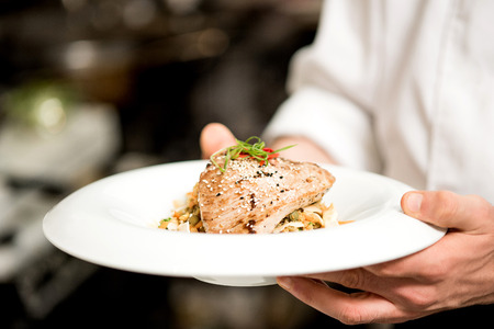 Chef holding the plate with tuna appetizer