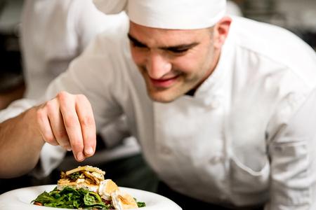 plating: Chef garnishing a salad of roast goat cheese