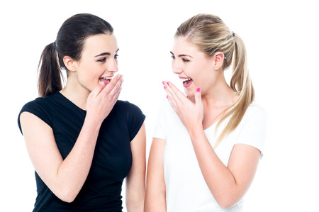 laughing out loud: Surprised young girls laughing out loud over white
