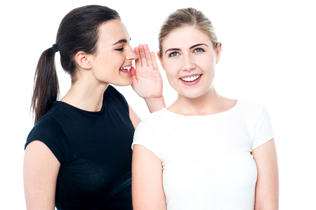 pretty teen: Two pretty smiling girls sharing a secret Stock Photo