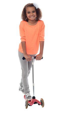 어린 소녀: Little girl riding with her scooter bicycle