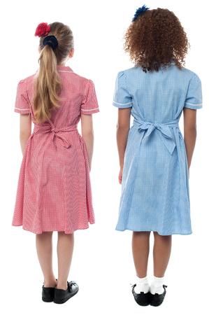 jolie petite fille: Pleine longueur des écolières en uniforme face au mur Banque d'images