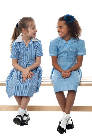 niños sentados: Niñas de la escuela sentado en el banco, hablando juntos Foto de archivo