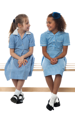 mixed race children: School girls sitting on bench, talking together