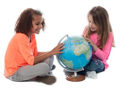 ni�as peque�as: Las ni�as sentados en el piso y jugando con un globo Foto de archivo