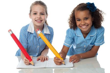 school exam: School girls writing homework together Stock Photo