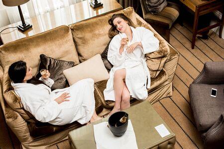 lap of luxury: Two women enjoying drinks after spa bath.