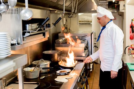 kitchen aprons: Male chef cooking with flame in a frying pan on kitchen