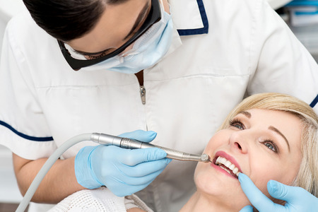 curing: Female dentist curing a patient teeth in clinic Stock Photo