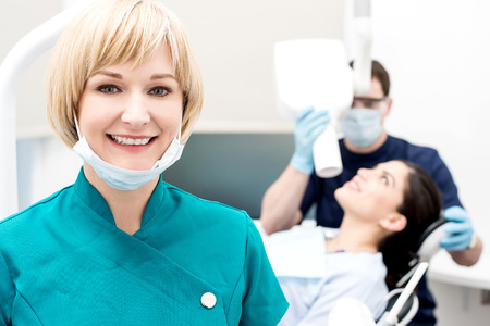 Woman assistant posing, behind dentist treating patient Standard-Bild