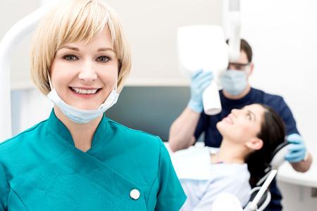 paciente: Mujer asistente posando, detrás de dentista paciente el tratamiento Foto de archivo