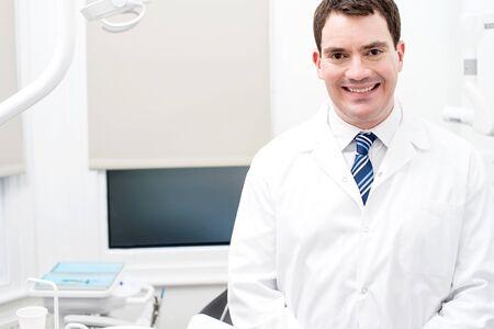 dentista: Dentista hombre feliz que presenta en la clínica dental