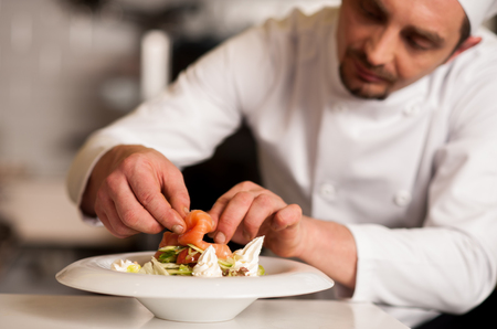 Chef adding topping for smoked salmon salad Foto de archivo
