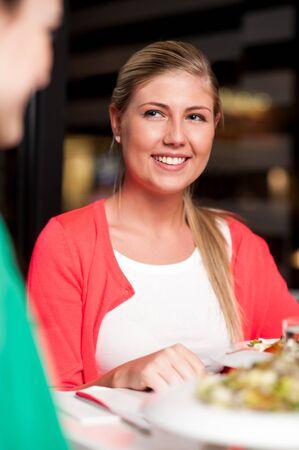 relishing: Best friends enjoying meal in a restaurant