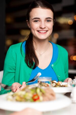 relishing: Smiling cheerful young posing to camera at dinner