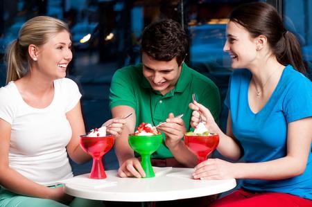 relishing: Three friends having deserts in a restaurant