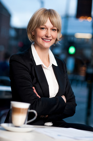 Happy business lady posing in restaurant with crossed arms photo