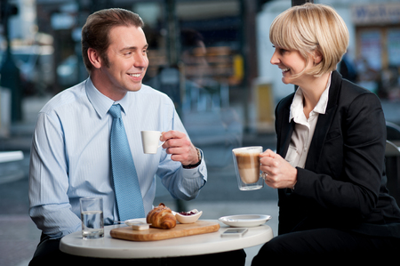Happy business partners having coffee at cafe photo