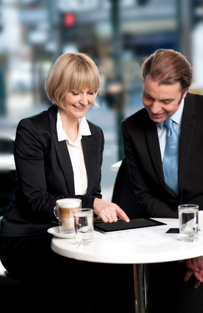 Business people discussing using tablet PC at cafe photo