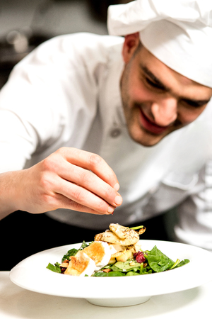 plating: Happy chef garnishing a salad of roast goat cheese