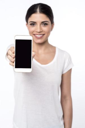 the latest: Beautiful girl showing latest smartphone Stock Photo