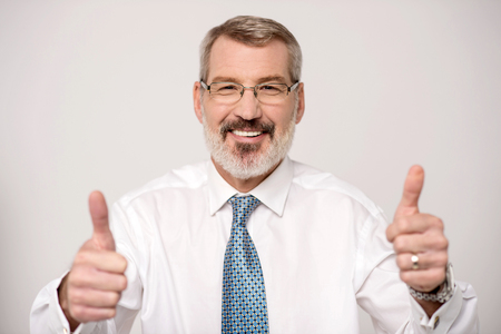 Male executive showing thumbs up sign Stock Photo