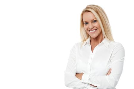 femmes souriantes: femme professionnelle posant sur fond blanc, les bras croisés Banque d'images