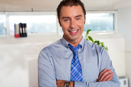 Cheerful male executive posing, arms crossed photo