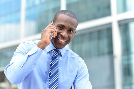 personas comunicandose: Ejecutivo de sexo masculino feliz que habla usando el teléfono celular