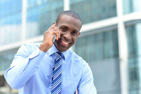 communicating: Happy male executive speaking using cell phone Stock Photo