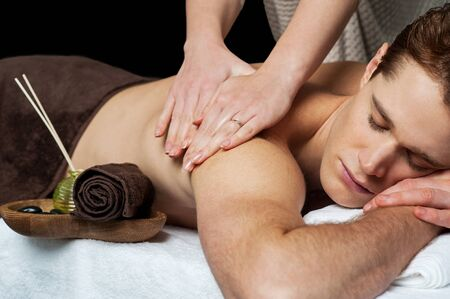 lastone therapy: Young man getting massage at a spa saloon Stock Photo