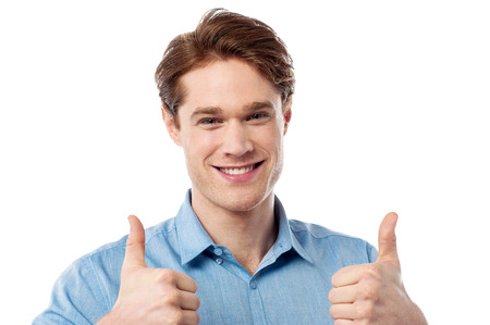 posing  agree: Smiling young guy showing double thumbs up sign