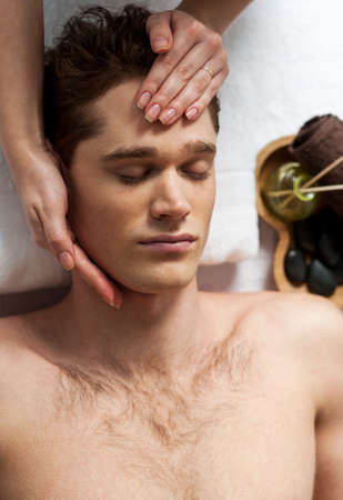 day spa: Relaxed man getting a face massage at day spa