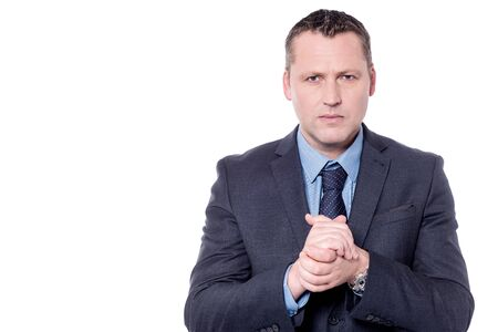 clasped: Serious businessman with clasped hands over white
