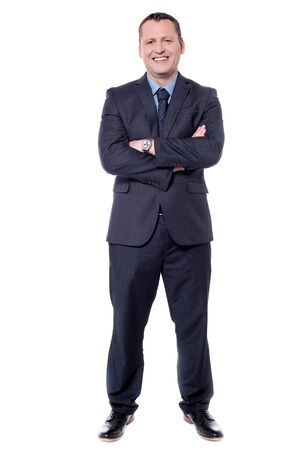 folded arms: Confident businessman isolated on white with folded arms