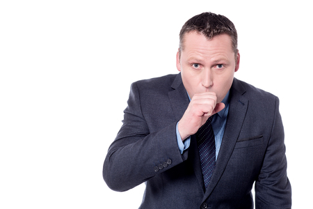 Businessman raising his fist to mouth looking miserable unwell
