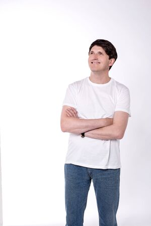 folded arms: Casual man looking up with folded arms