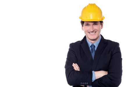 folded arms: Businessman posing with folded arms wearing safety helmet Stock Photo