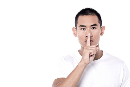 shush: Young man with finger on lips asking for silence