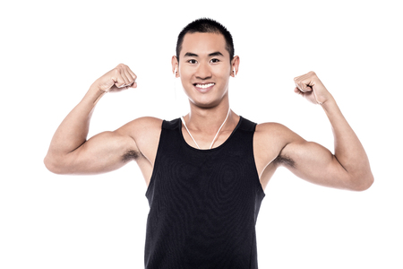 ear phones: Muscular man flexing his biceps with ear phones