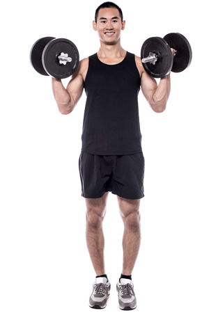 powerful: Powerful young man lifting weights over white Stock Photo