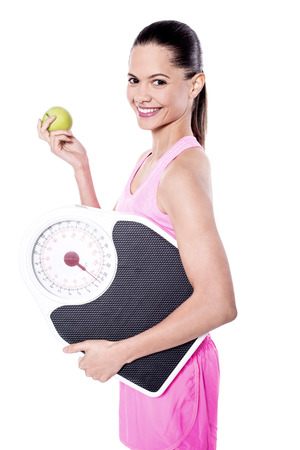 Trainer posing with apple and weigh scale