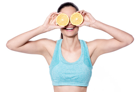 armpits: Fit young woman showing sliced orange