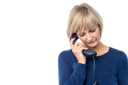 discouraged: Sad woman talking on the phone