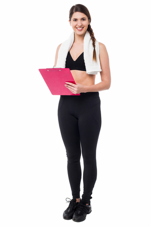 documenting: Young fit trainer holding a clipboard