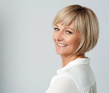 looking over: Smiling middle aged lady looking over shoulder Stock Photo
