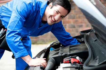 bonnet: Young male mechanic fixing car bonnet Stock Photo